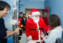 Los bomberos de Huelva ayudan a Papá Noel en su visita a los pacientes del Hospital Juan Ramón Jiménez